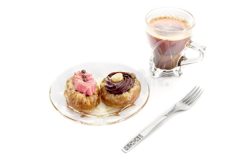 Two cakes and a cup of coffee. Two small cakes `roxakia` with syrup on a plate and a cup of coffee close-up against white background Greek cuisine stock photo