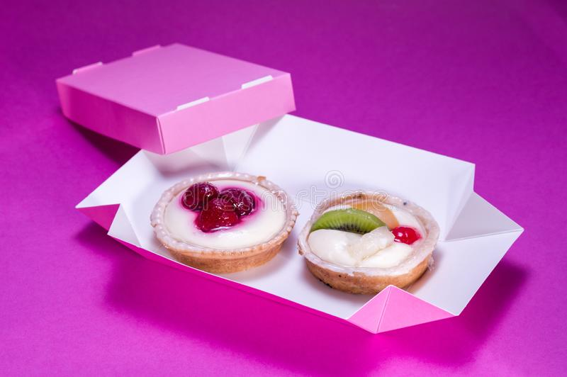 Two cakes in a pink box. Dessert delivery. Pastries with fruit and cream. View at an angle royalty free stock photo
