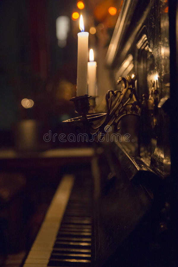 Two candles in candlesticks attached to the wall of black piano. Two lighted white candles in old candlesticks attached to the wall of black piano with the lid royalty free stock photo