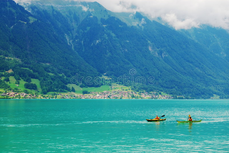 Two canoes on a lake. In front of green mountains and an authentic village. Interlaken, switzerland, europe stock photography