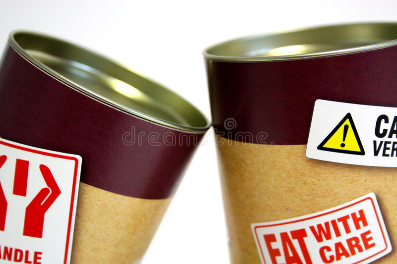 Two cans with fat warning stickers stock photo