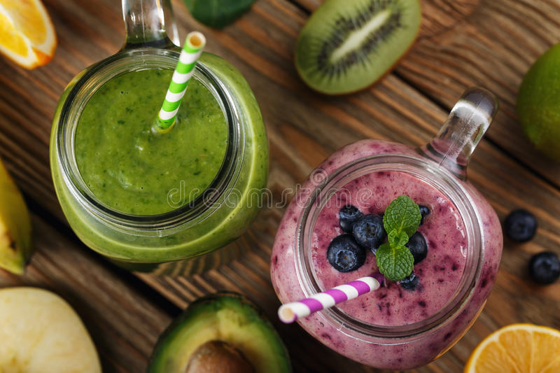 Two cans of smoothies made of blueberries, bananas, orange. And apple, kiwi and avocado, top view, close-up royalty free stock image