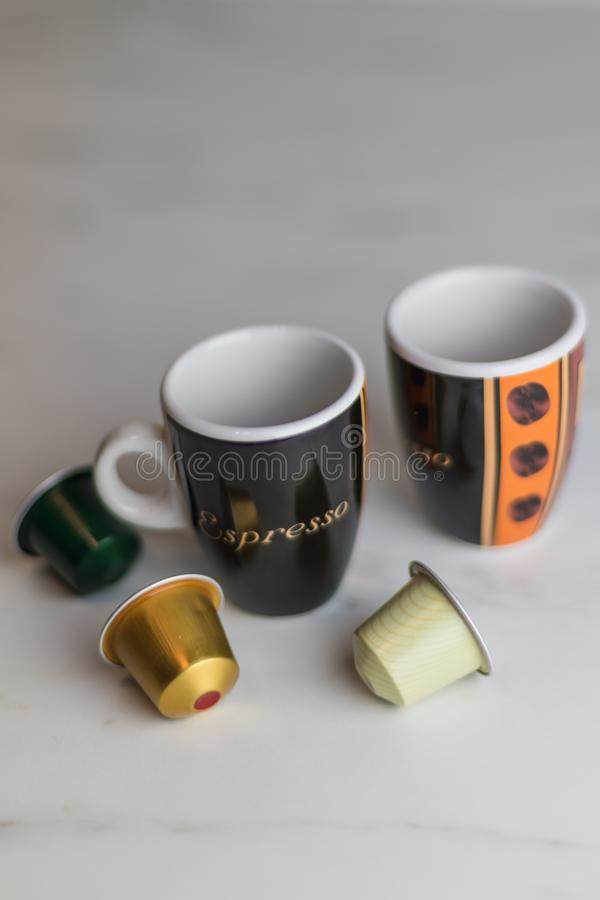 Two cappuccino cups with colorful capsules on a marble table stock photography