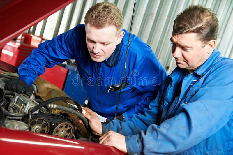 Two car mechanic diagnosing auto engine problem royalty free stock image