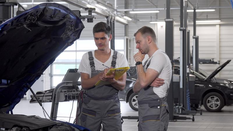 Two car mechanics discussing automobile with open hood. Male technicians in grey uniform working at the garage, looking under the hood of a broken car. Service stock photography