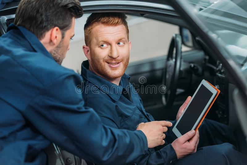 Car mechanics using digital tablet. Two car mechanics sitting in a car at workshop using a digital tablet stock photo