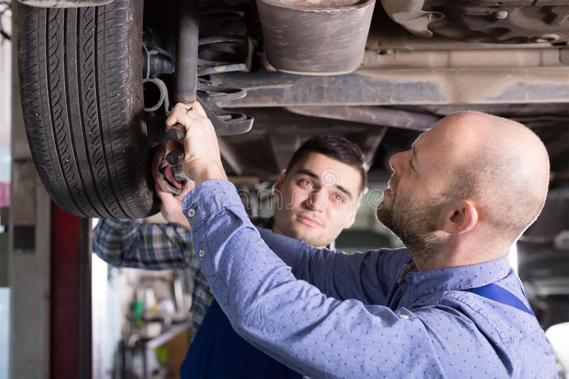 Two car mechanics at workshop. Two serious car mechanics checking up pressure in tires at garage royalty free stock photography