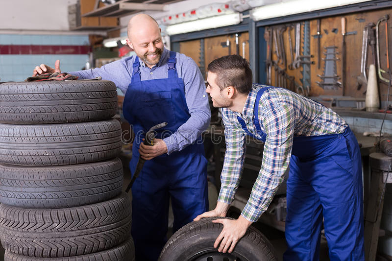 Two car mechanics at workshop. Two smiling car mechanics working together at workshop. Focus on brunet royalty free stock photo