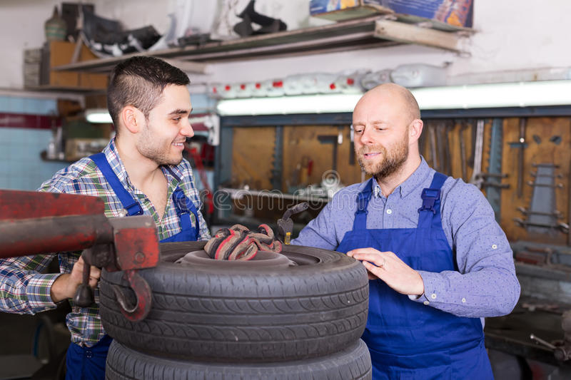 Two car mechanics at workshop. Two successful smiling car mechanics working together at workshop royalty free stock photos