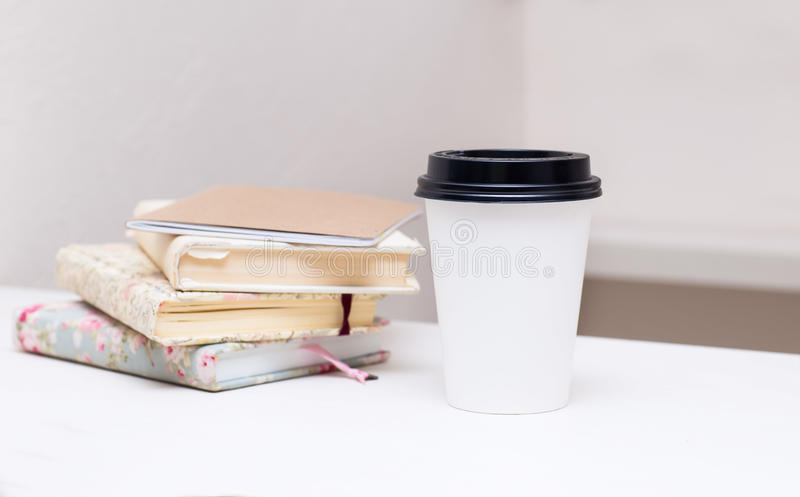 Two cardboard cups are a number of books on the table royalty free stock image