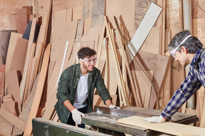 Two carpenters cooperating and woodworking royalty free stock photos