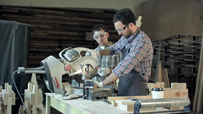 Two carpenters works on woodworking machine in workshop. royalty free stock photo