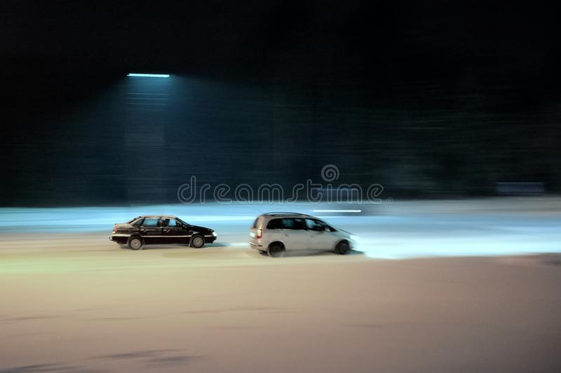 Two cars drive at night in winter royalty free stock photo
