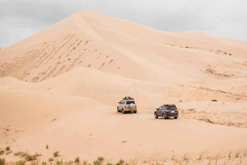 Two cars driven through sand dunes in Gobi desert. South east of Mongolia royalty free stock photos
