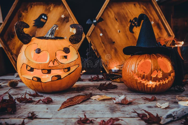 Two Carved pumpkins and other symbols of Halloween on wooden background. Halloween pumpkin head jack lantern with scary evil faces. Spooky holiday concept royalty free stock photo