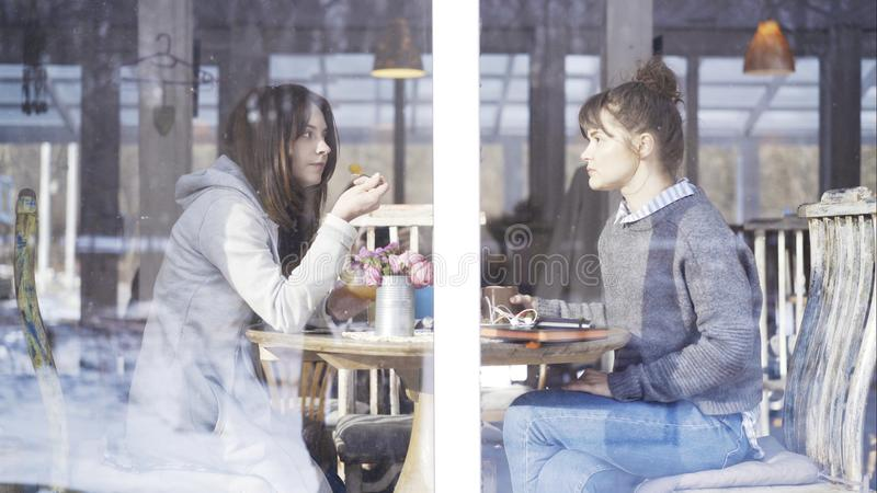 Two female friends meeting in a cafe to talk stock photos