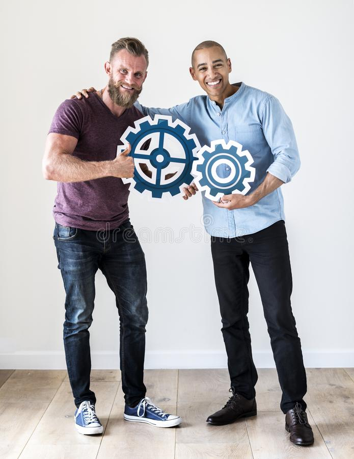 Two casual man holding cog icon stock image
