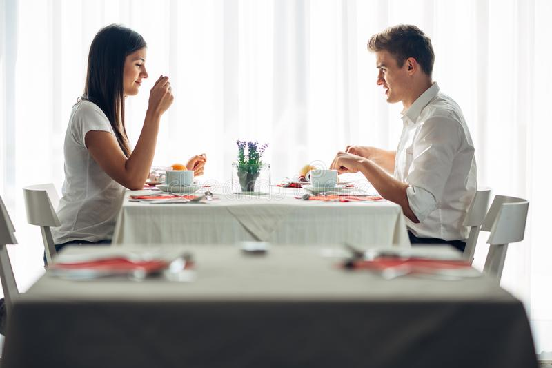 Two casual young adults having a conversation over a meal.Formal proposal,talking in a restaurant.Trying food,offers,special menu. Happy couple eating course in stock photo