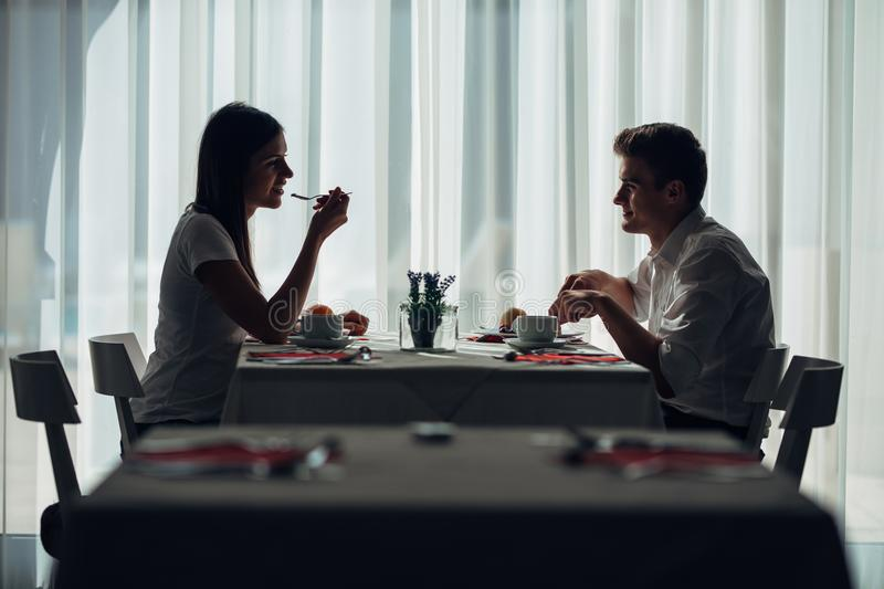 Two casual young adults having a conversation over a meal.Formal proposal,talking in a restaurant.Trying food,offers,special menu. Happy couple eating course in stock photography