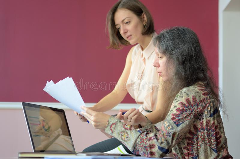 Two casually dressed young ladies models sit on a desk in a vintage office and discuss model release documents royalty free stock photo