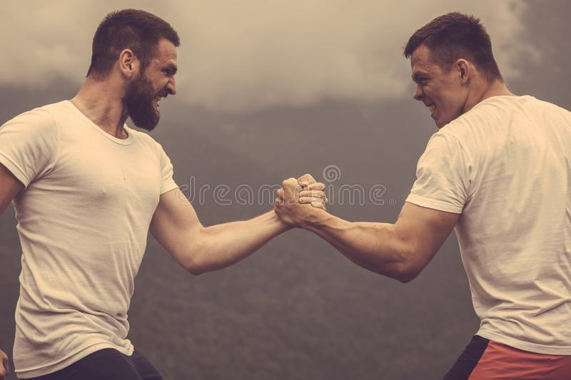 Two caucasian athletes in sportive wear measuring forces at outdoor training. Strong male bodybuilders in white t-shirts greeting each other in wrestling manner royalty free stock photography