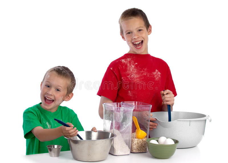 Two caucasian brothers baking a cake. Two beautiful caucasian brothers making a cake in the kitchen, smiling happily, isolated on white background stock photo