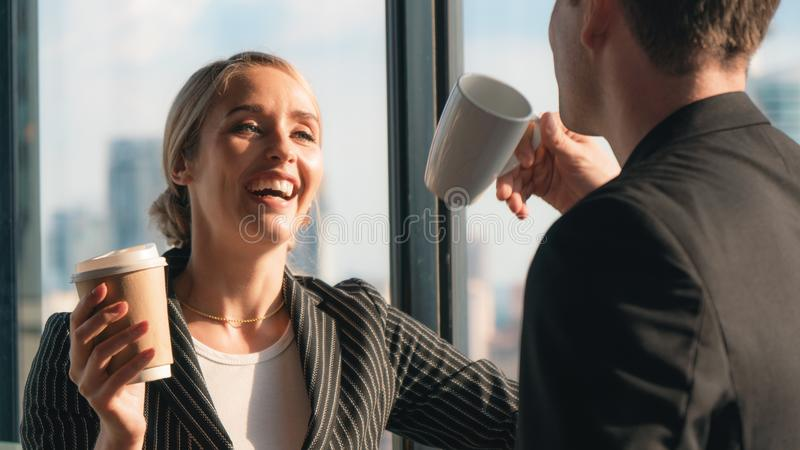 Two caucasian business people look happy while having business talk and drinking coffee in office stock images