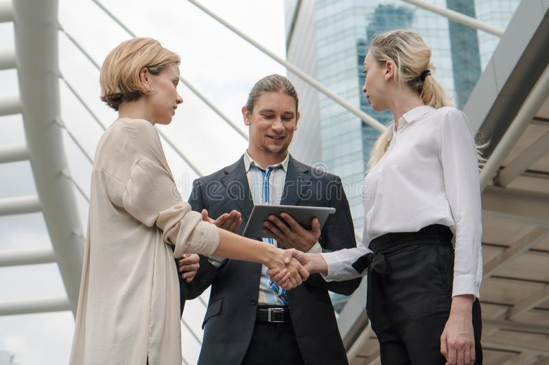 Two caucasian business woman having handshake to have greeting with caucasian businessman standing with tablet on hand. Two caucasian business women having stock photo