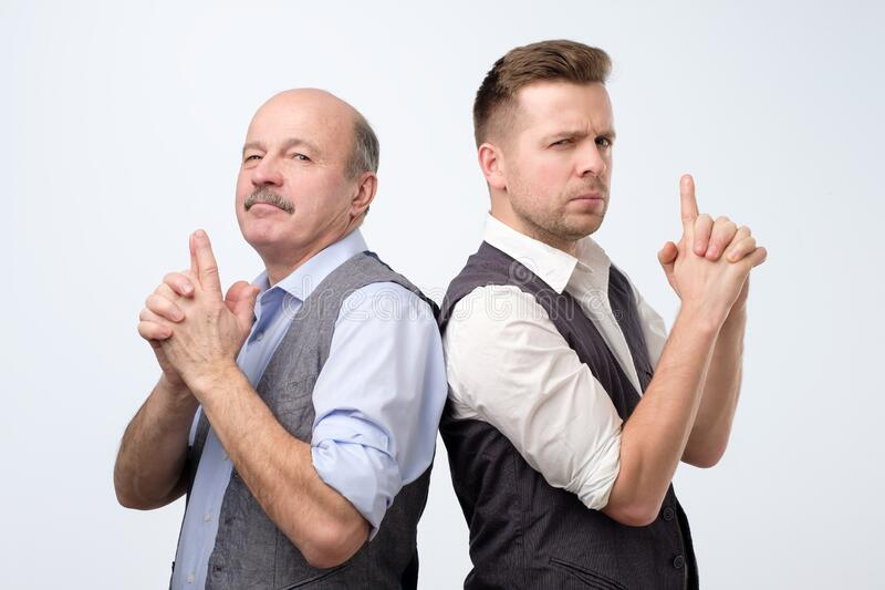 Two caucasian businessman doing a gun gesture getting ready to shoot and acting like a secret agent stock photos