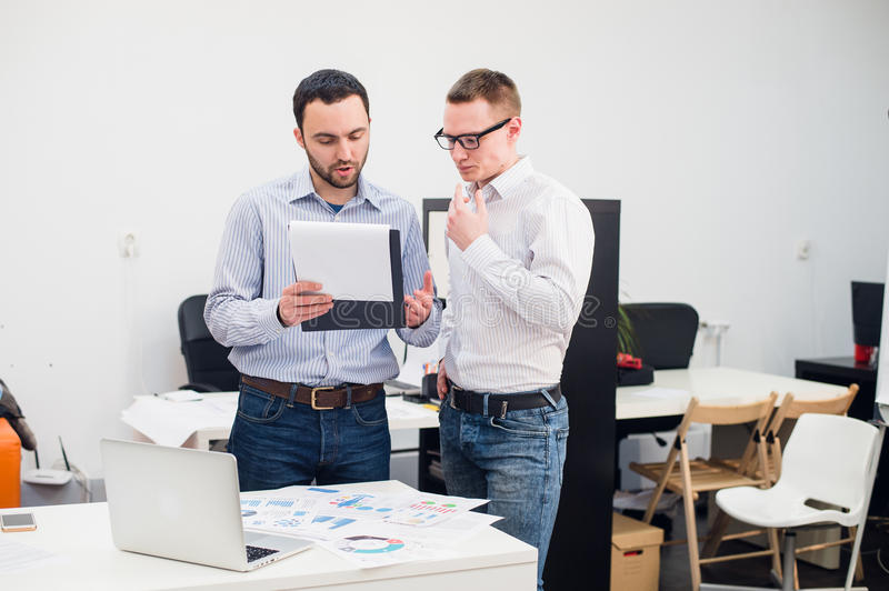 Two caucasian corporate executives in casual wear having a business discussion in office. stock photo