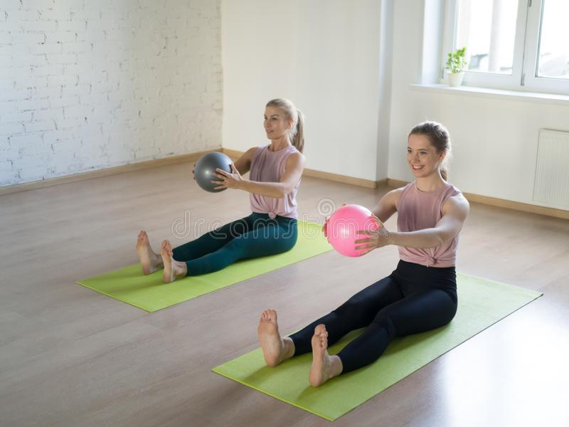 Two caucasian girls practise pilates with small fit balls, in fitness studio, loft style, selective focus. Two caucasian girls practise pilates in fitness royalty free stock images