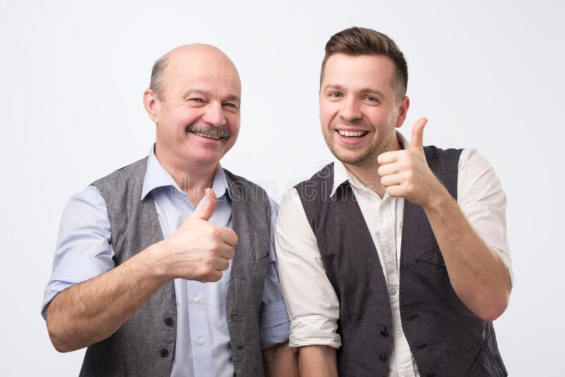 Two caucasian mature men father and son holding thumbs up approving your choice royalty free stock photography