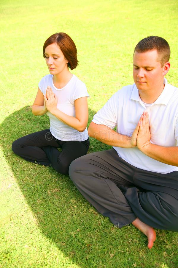 Two Caucasian Meditate On Grass royalty free stock photo
