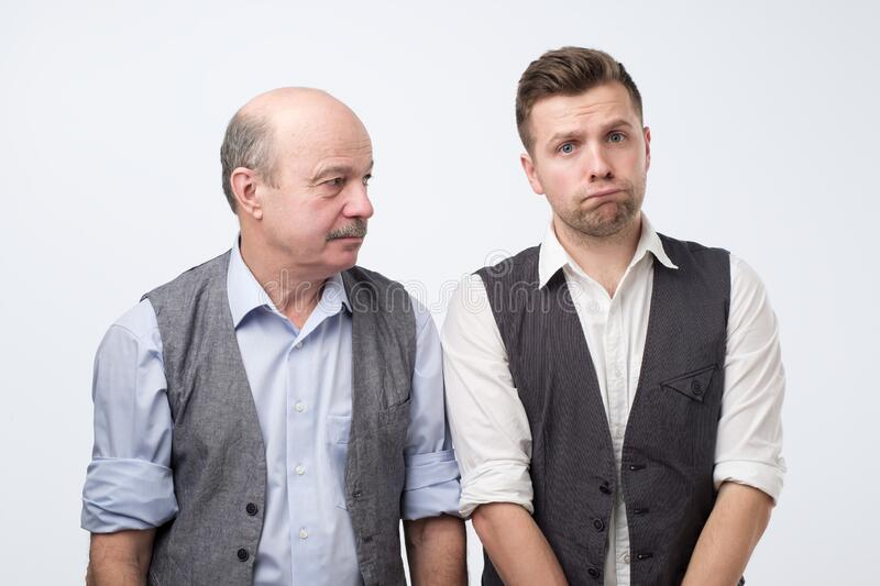 Two caucasian men father and son sulking and frowning eyebrows, being offended with cruel words. royalty free stock images