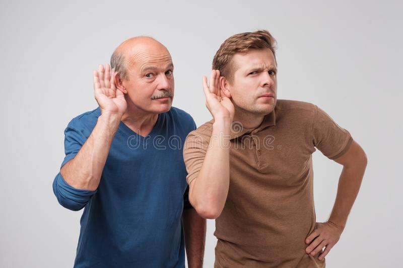 Two caucasian men hearing with hand on ear isolated on a white background. Please speak loudly. royalty free stock image