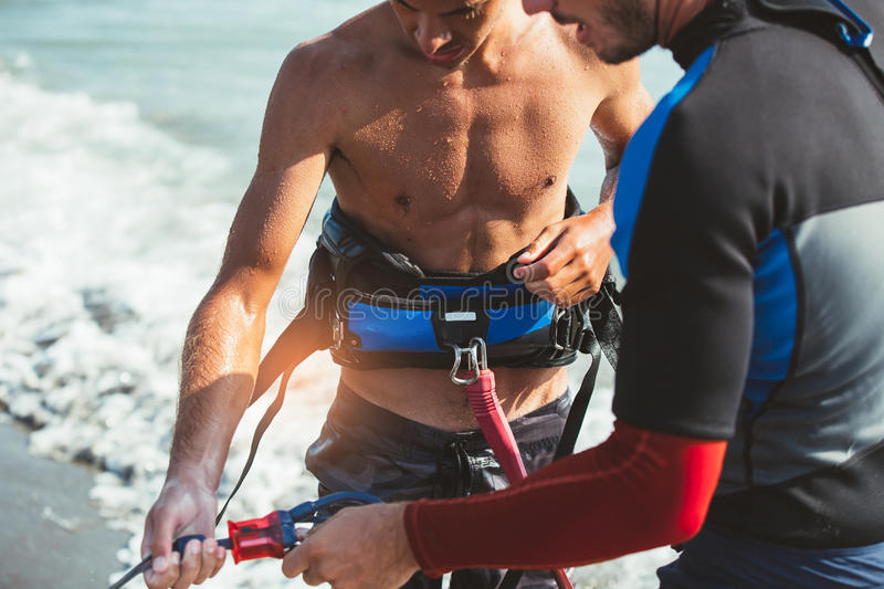 Two Caucasian men kitesurfers preparing equipment stock images