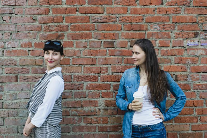 Two caucasian women girlfriends stand on grange red brick wall background. Two caucasian women girlfriends stand near old grange red brick wall background in royalty free stock photo