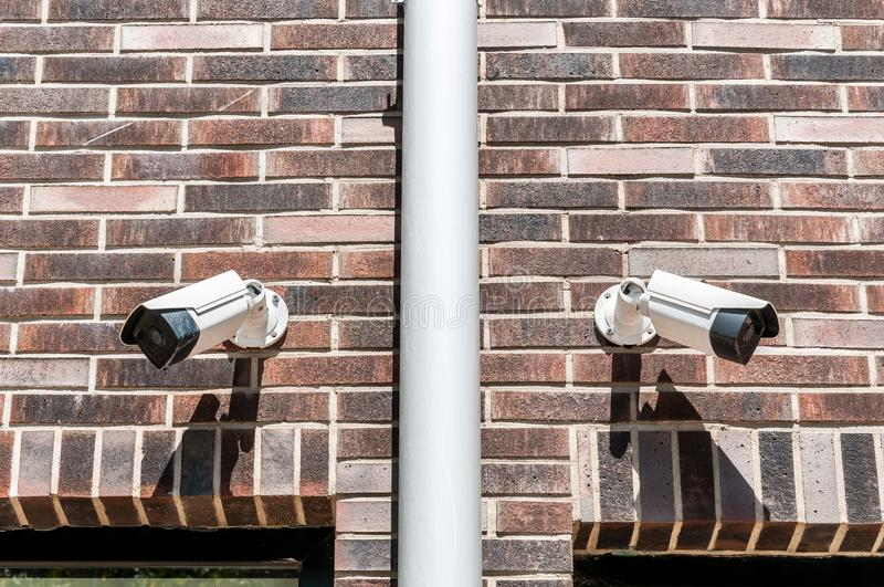 Two cctv surveillance security system cameras on the brick wall of luxury residential building for safety stock photo