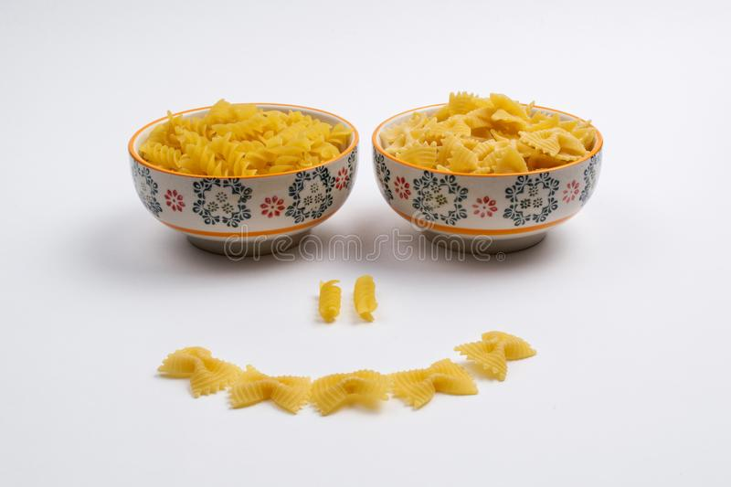 Two ceramic bowls full of pasta make up a smiling face royalty free stock photography