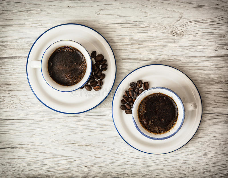 Two ceramic cups of coffee on the wooden background. Coffee beans. Stylish still life. Refreshment theme stock photography