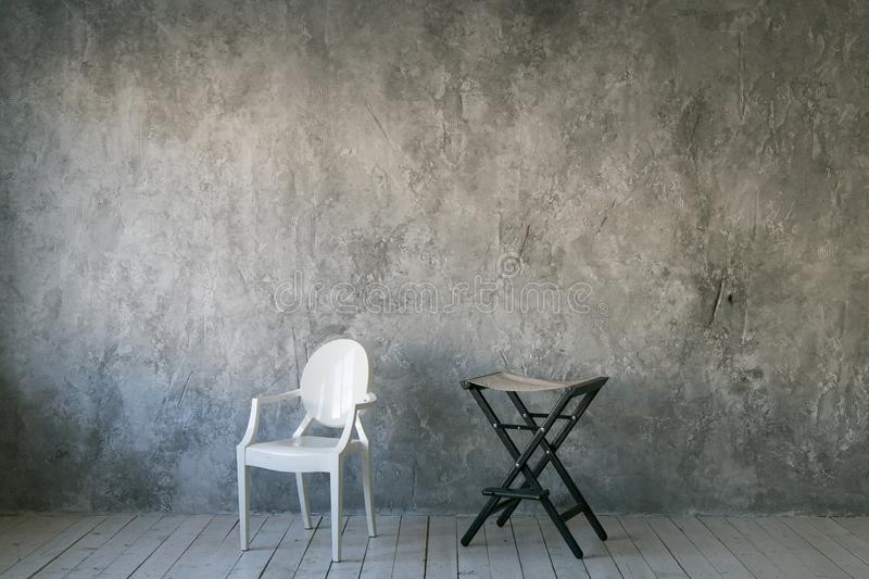 Two chairs against the gray concrete wall. Room in loft style. Wooden floor. Daylight. Free space for text. Two chairs against the gray concrete wall. Room in royalty free stock photo