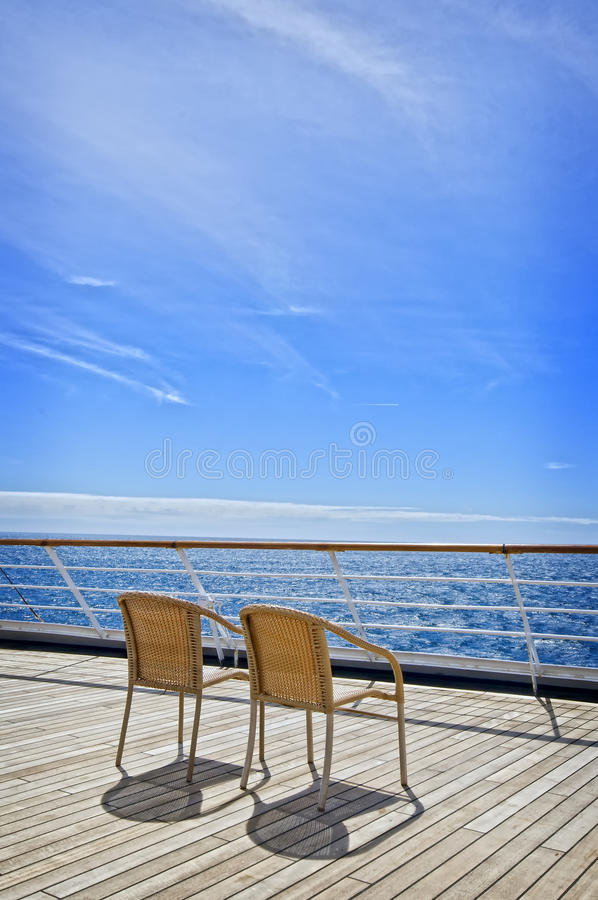 Two Chairs on a Cruise Ship Deck. Two woven chairs on the wooden deck of a cruise ship waiting for two people to sit down, relax, and watch the beautiful blue stock image