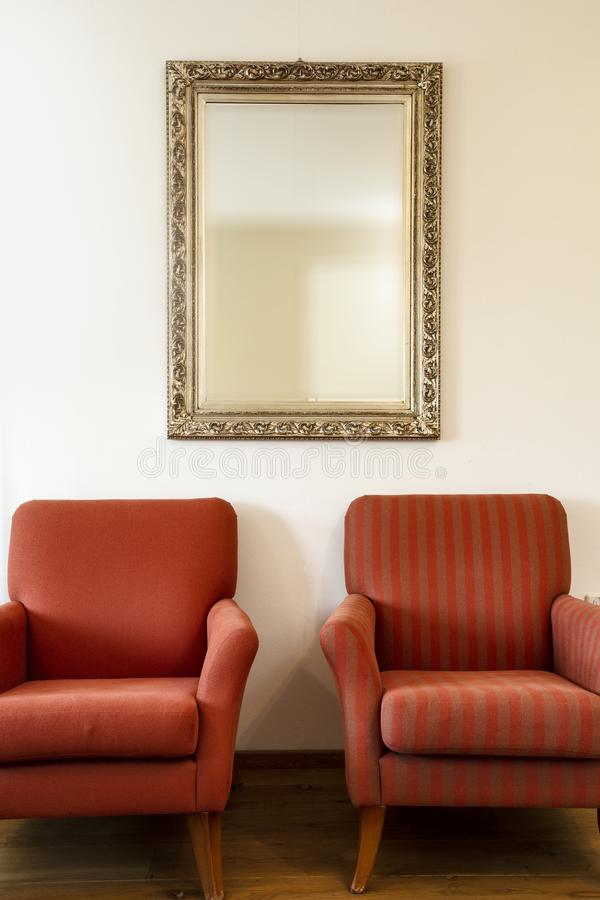 Two chairs and golden framed mirror on a white wall with soft natural light coming in from outside. beauty stock image