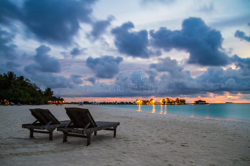 Two chairs on the Maldivian beach at beautiful sunset stock image