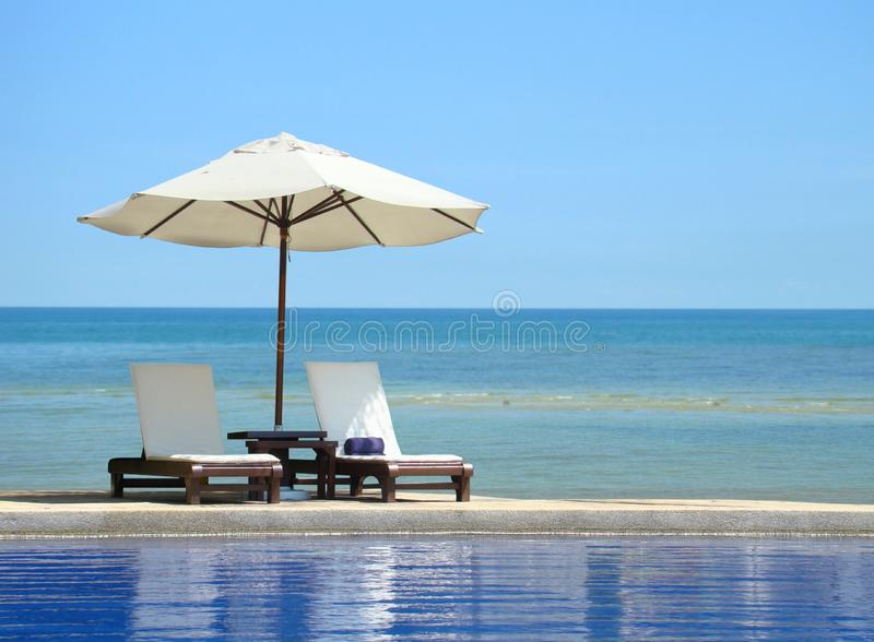 Two chairs and white umbrella on the beach royalty free stock images