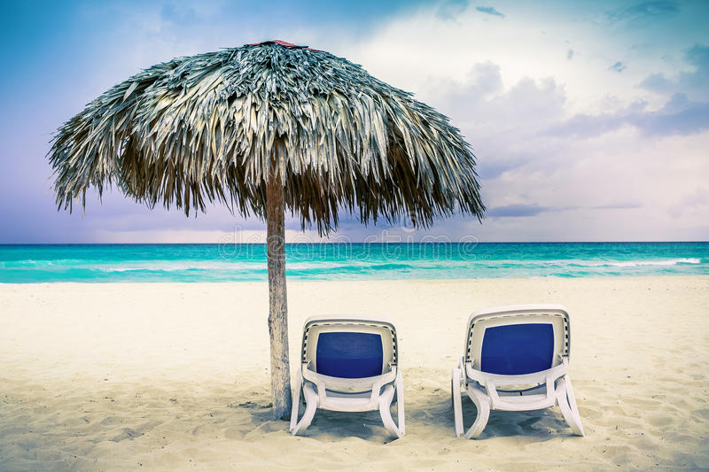 Two chaise lounges on the beach stock photos
