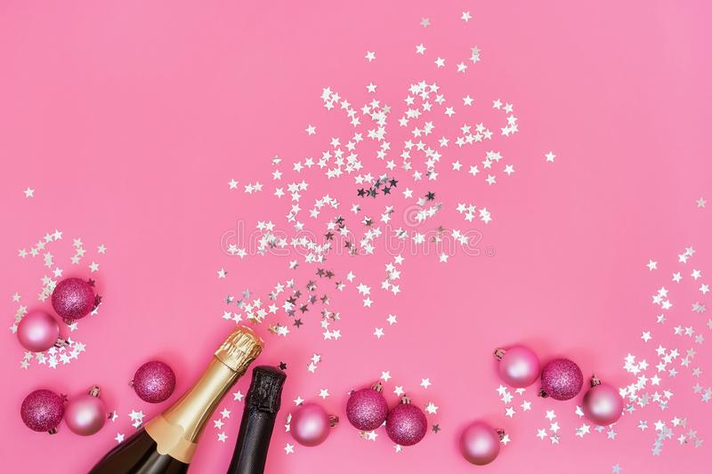 Two Champagne bottles with Christmas ornaments on pink background. Copy space, top view, flat lay stock photography
