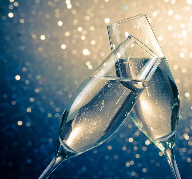 Two champagne flutes with golden bubbles on blue light bokeh background. Two champagne flutes with golden bubbles make cheers on blue light bokeh background with stock images