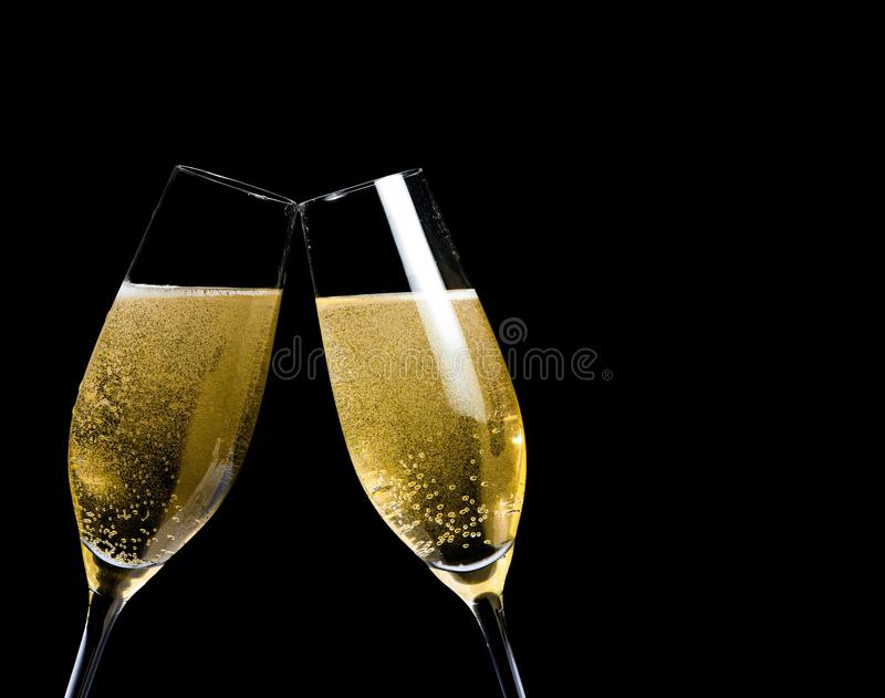 Two champagne flutes with golden bubbles make cheers on black background. With space for text stock image