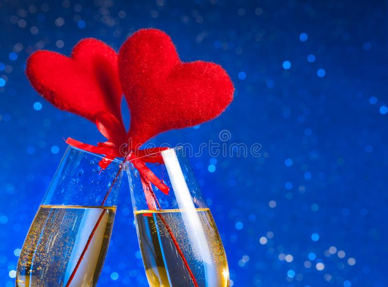 Two Champagne Flutes With Golden Bubbles And Red Velvet Hearts Make Cheers On Blue Bokeh Background Stock Image